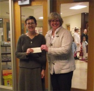 Amy Lutzke presents St. Joe's Principal Kari Holm with a check for $500.